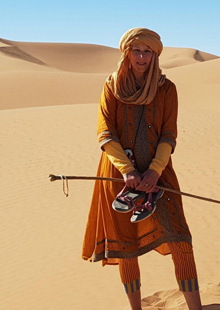 Isabel von Roon steht lächelnd barfuß und mit Turban auf dem Kopf in den Dünen