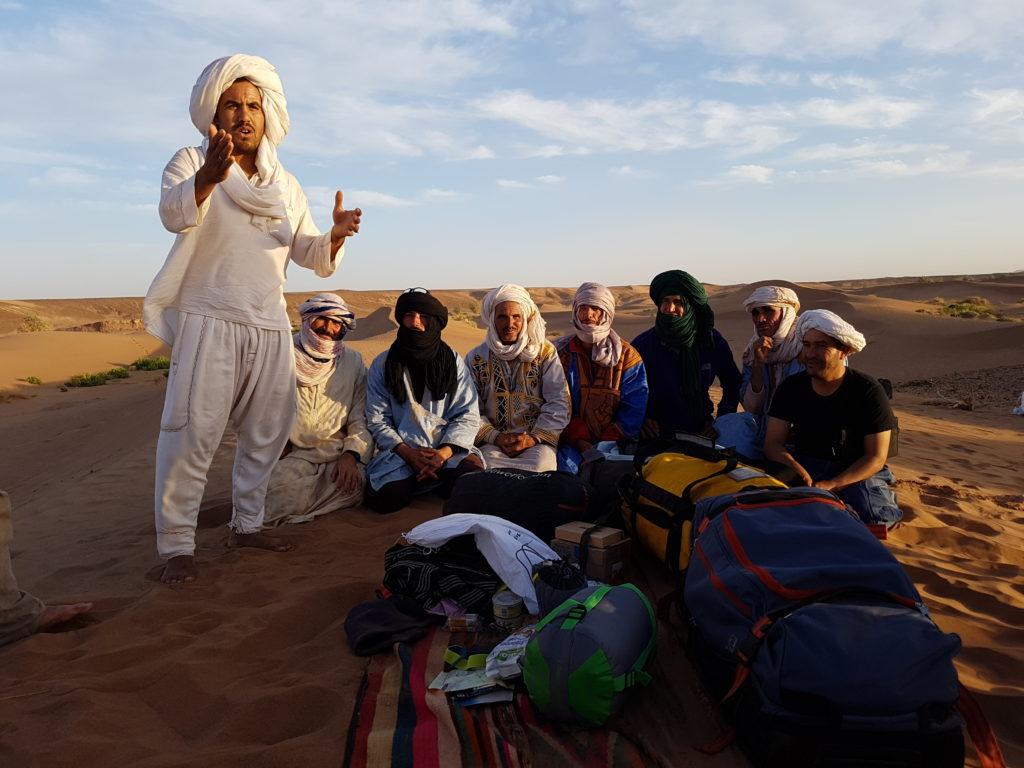Nomaden sitzen auf einer Düne, vor ihnen steht Brahim und spricht in die Kamera
